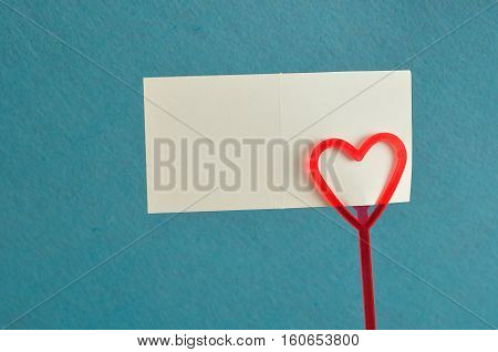 Valentines day. A note holder with a red heart with an empty card isolated against a blue background