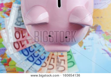 Pig moneybox and Euro banknotes on world map background, top view