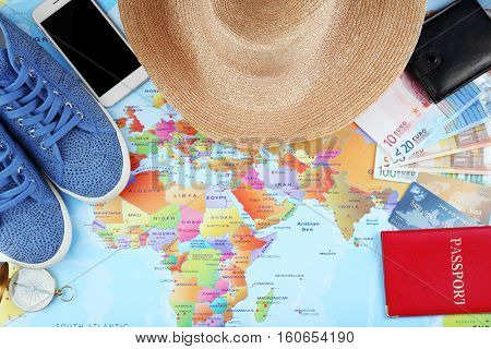 Traveller's accessories on world map background, top view