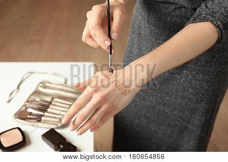 Female visagiste applying cosmetics onto hand