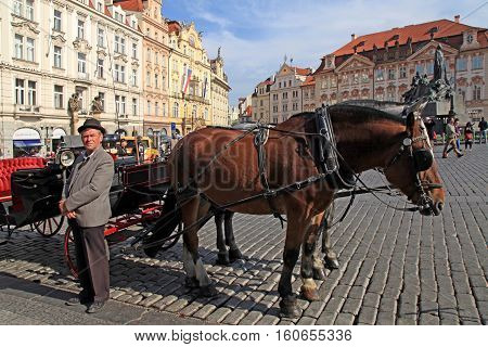 PRAGUE, CZECH REPUBLIC - OCTOBER 4, 2015: Horse drawn carriage and cabman on Old Town square in Prague, Czech Republic.
