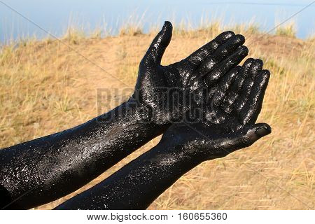 Therapeutic mud / Hands covered with therapeutic mud. Salt lake in the Altai region.