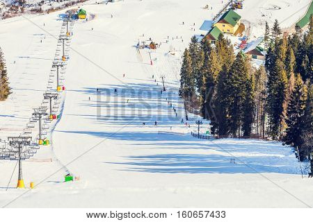 Ski riders on a cable chair lift in cloudy snowy winter mountains close up
