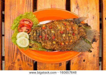 Grilled carp gourami fish with herbs tomatoes cucumber and chili pepper