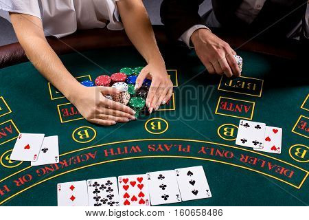 couple playing poker at the table. The blonde girl and a guy in a suit. close up hands. take chips won