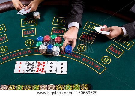 couple playing poker at the table. The blonde girl and a guy in a suit. close up hands. man bets chips