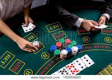 couple playing poker at the table. The blonde girl and a guy in a suit. close up hands. woman bets chips