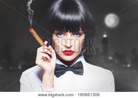 Sexy mafiosi woman boss in tux smoke with cigar in town