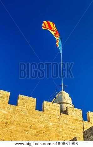 Flag of the Valencian Community on Serranos Gate in Valencia, Spain