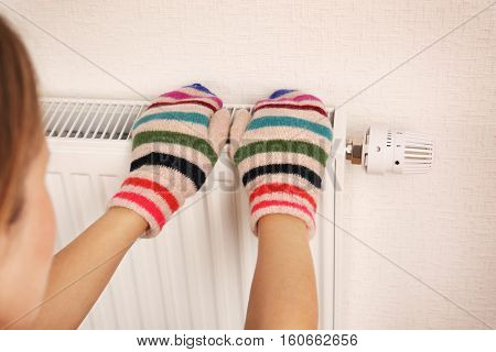 Woman in knitted mittens touching heating radiator indoors