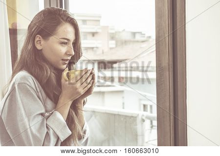 young woman drinks coffee at the window in a cold winter morning warming up with the hot beverage. concept of freedom and relaxation