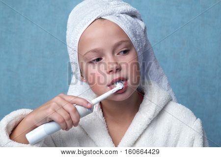 Close up cute little girl in a bath towel on the head and a white bathrobe cleaning teeth with electrical toothbrush against cool blue wall
