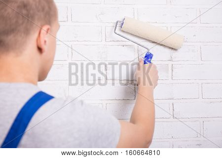 Back View Of Young Man Painter In Workwear Painting Brick Wall With Paint Roller