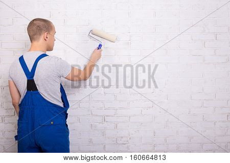 Back View Of Man Painter In Workwear Painting Brick Wall With Paint Roller And Copy Space
