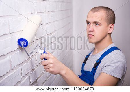 Man Painter In Workwear Painting Brick Wall With Paint Roller