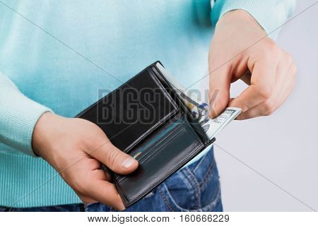 man holding a leather wallet with money