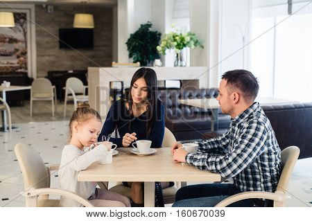 Family sitting together at table in a restaurant.