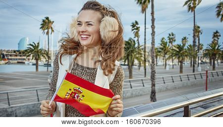 Woman On Embankment With Spanish Flag Looking Into Distance