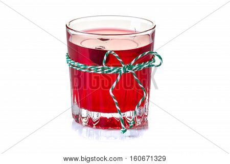 Glass of cranberry fruit drink isolated on white background and decorated with green-white rope