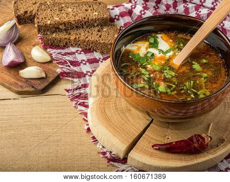 Tasty and nutritious borsch-soup with meat, potatoes, cabbage, tomatoes, beans, sour cream, parsley, onion, garlic, dark bread in a clay plate on a wooden tray and wooden table.