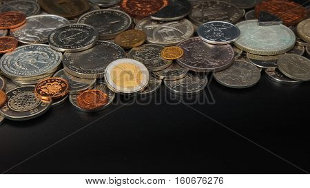 Top view of lot of coins of different countries of the world disordered on black table. Focus on 2 euros coin - Numismatics scene
