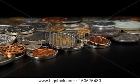 Side view of lot of coins of different countries of the world disordered on black table. Focus on 2 euros coin - Numismatics scene