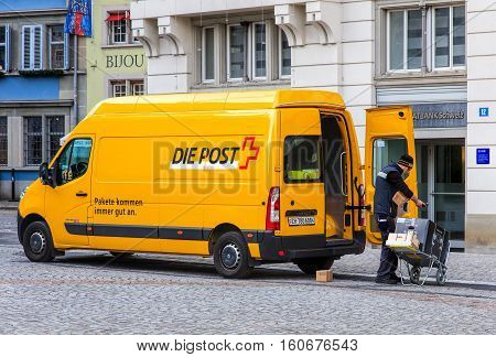Zurich, Switzerland - 11 December, 2015: Swiss Post postman offloading parcels from a van parked in the old town of the city. Swiss Post is the national postal service of Switzerland.