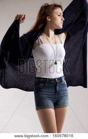 Beautiful young  brunette woman in blue sweater dress and jeans short on grey background. Autumn style the fashion