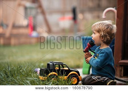 Boy with hose and machine. side view. boy looking away