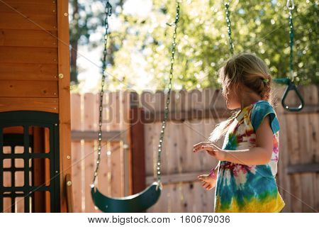 From below image of girl on swing. back view. girl on playground