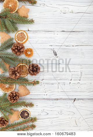 Christmas decoration on old whitre grunge wooden board backgrond with fur tree, cookies, pine cone and citrus vertical frame. Flat lay, top view