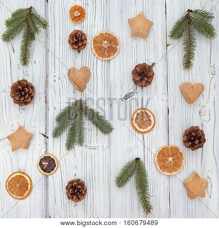 Christmas decoration on old whitre grunge wooden board backgrond with fur tree, cookies, pine cone and citrus. Flat lay, top view