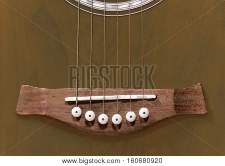 Close view of acoustic guitar bridge with saddle bridge pins and steel strings