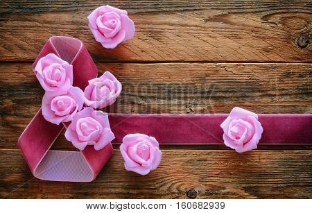 International Womens Day card velvet ribbon pink roses on old wooden boards 8 March composition