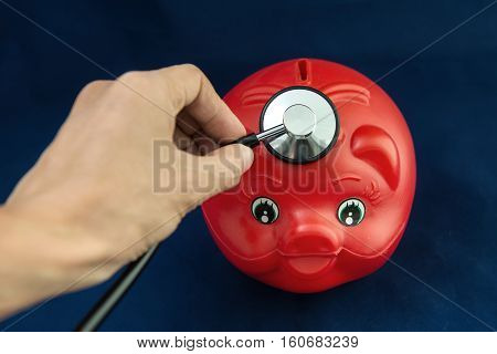 Piggy Bank and Stethoscope with Selective Focus on a blue Background.
