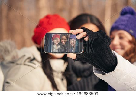 Group of millenial young female adult friends enjoying wintertime and in a snow filled park