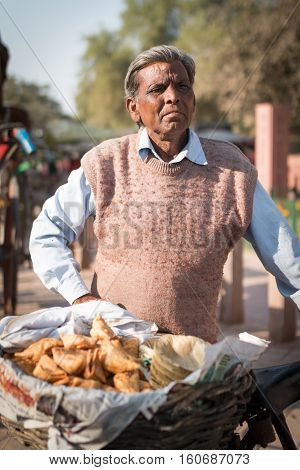 AGRA INDIA - Nov 14 2016: Local seller with traditional sweet bread or snack on bicycle standing for sell in front of Western Gate of Taj Mahal the monument of love on 27 November 2016.