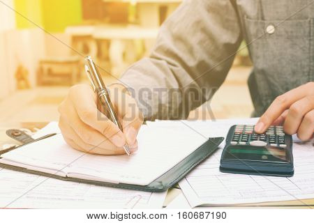 Young businessman analyzing finances with using calculator and writing note in home office.