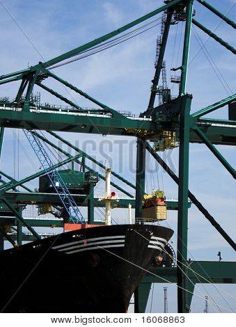 Container being transferred into a cargo ship at Antwerp harbor (brand names and logos have been removed)