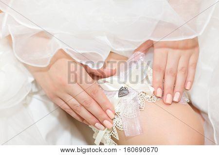 bride in wedding dress adjusts her garter
