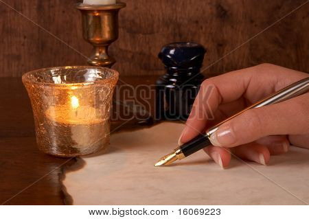 Hand writing on parchment with a golden fountain pen