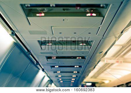 Airplane interior detail. Transportation background. Luggage shelf row.