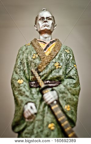 Samurai statue closeup. Ancient samurai statue with green kimono and katana sword.