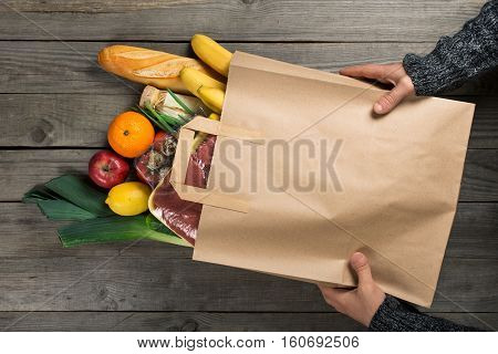 Man holding bag full of different healthy food on wooden kitchen table top view