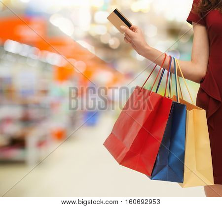 people, consumerism, finances and sale concept - close up of woman with shopping bags and credit card over supermarket background