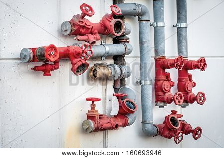 Metal water pipes. Red valves. Fire hydrant system.