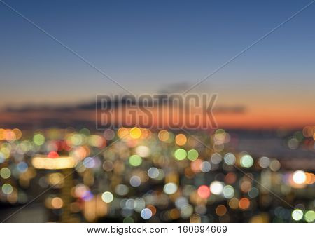 Colorful blurred skyline with city bokeh lights illuminated at sunset