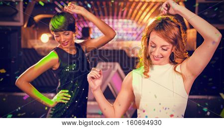 Smiling female friends dancing on dance floor against flying colours