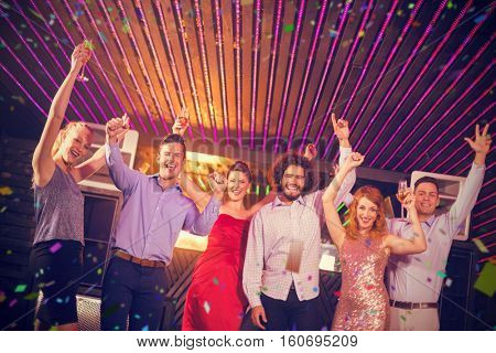 Smiling friends dancing on dance floor against flying colours