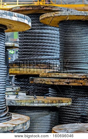 Large cable reels stocked in the factory premises. Workshop production of cable slings. Industrial abstract background.